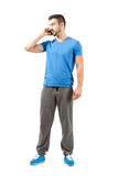 Young fit male in sweatpants talking on the phone Stock Photos