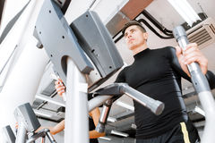 Young fit male working out on an elliptical trainer Royalty Free Stock Image
