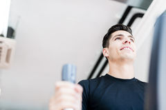 Young fit male working out on an elliptical trainer Stock Photography