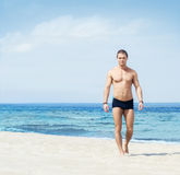 Young and fit man on the beach Royalty Free Stock Image