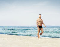 Young and fit man on the beach Stock Images