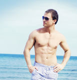Young and fit man on the beach Stock Photography