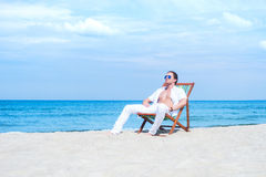 Young and fit man chilling on the beach Royalty Free Stock Image