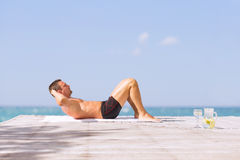 Young fit man doing abs crunches exercise outdoors royalty free stock photo