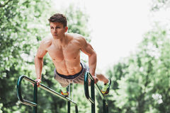 Young fit man doing push ups on bars. In an outdoors gym Royalty Free Stock Images