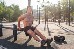 Young fit man doing triceps dips exercises during outdoor cross training workout. Fitness male model. Young fit man doing triceps dips exercises during outdoor Stock Images