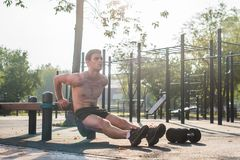 Young fit man doing triceps dips exercises during outdoor cross training workout. Fitness male model. Young fit man doing triceps dips exercises during outdoor Royalty Free Stock Images