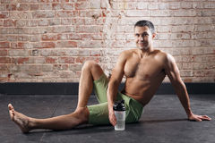 Young fit man drinking water. exercising in a gym on old red bricks background Stock Photos