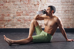 Young fit man drinking water. exercising in a gym on old red bricks background Royalty Free Stock Photos