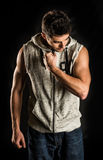 Young fit man flexing his bicep isolated on black background Stock Images