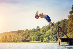 Young fit man jumping into a lake. From a wooden jetty. Water sport. Side view Stock Photo