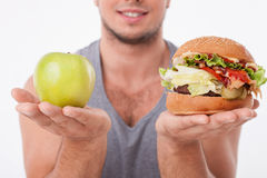 Young fit man is making decisions about food stock photo