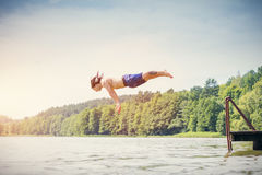 Young fit man making a jump into a lake. Young fit man making a jump into a lake from a wooden jetty. Water sport. Side view Stock Photo