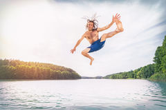 Young fit man making a jump into a lake. Looking into the camera. Nature and summer activity. Water sport Royalty Free Stock Image
