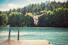 Young fit man making a jump into a lake. Young fit man making a jump into a lake from wooden jetty. Water sport. Nature and outdoor activity royalty free stock photography