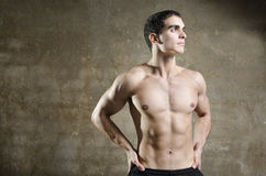 Young fit man posing on dirty wall background Royalty Free Stock Photos