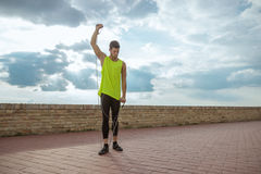 Young fit man resistance band outdoors training arm up Stock Photo