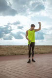 Young fit man resistance band outdoors training arm up Stock Images