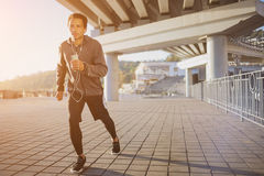 Young fit man running at outdoors, autumn and listening music, attractive dark skinned runner jogging fast, sport Royalty Free Stock Images