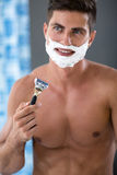 Young fit man with shave foam on face Stock Photo