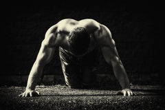 Young fit man showing his muscles. Toned and stylized photo Stock Image