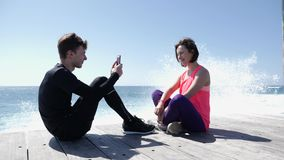 Young fit man sitting on the beach taking picture of his girlfriend with the phone. Strong waves splashing against the rocks. Young fit man sitting on the beach stock footage