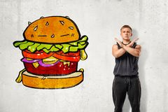 Young fit man in sleeveless hoody standing with arms crossed across chest at white wall with drawing of huge hamburger. On it. Say no to junk food. Keep fit royalty free stock photography