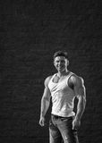 Young fit man is smiling and showing muscles Royalty Free Stock Photo