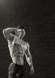 Young fit man is smiling and showing muscles Stock Image