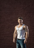 Young fit man is smiling and showing muscles Royalty Free Stock Photography
