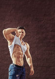Young fit man is smiling and showing muscles Stock Images
