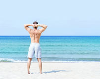 Young, fit man standing on a summer beach Stock Photo