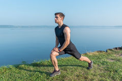 Young fit man stretching legs outdoors doing forward lunge. Young fit man stretching legs outdoors doing forward lunge Royalty Free Stock Images