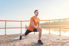 Young fit man stretching legs outdoors doing forward lunge. Young fit man stretching legs outdoors doing forward lunge Stock Image
