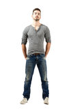 Young fit man in v-neck t-shirt, torn jeans and sneakers. Standing with hands in back pocket. Full body length portrait isolated over white background royalty free stock photography