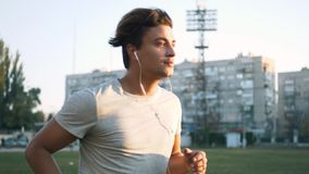 Young fit mixed race man listening to music and working out by running on urban stadium track stock video