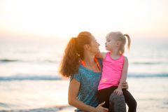 Young fit mother smiling with daughter on her knee on beach Royalty Free Stock Photos