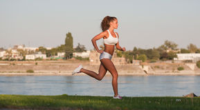 Young and fit. Musclular fit young brunette woman enjoying workout in nature Royalty Free Stock Image