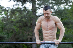 Young fit muscular man doing exercises on the horizontal bar Stock Photos