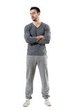 Young fit muscular sporty man with crossed arms looking down. Full body length portrait isolated on white studio background stock photo