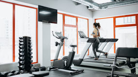 Young fit pretty woman doing exercises on the treadmill Royalty Free Stock Photo