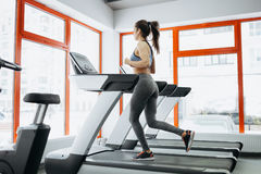 Young fit pretty woman doing exercises on the treadmill Stock Photos