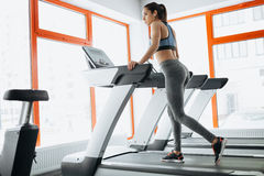 Young fit pretty woman doing exercises on the treadmill Stock Photography
