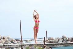 A young and fit redhead woman posing on a dock Royalty Free Stock Image