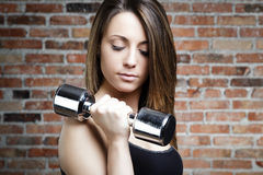 Young fit serious woman lifting dumbbells Royalty Free Stock Photos