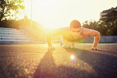 Young fit shirtless man doing push-ups outdoors. Young fit shirtless Caucasian man doing push-ups outdoors on sunny summer day. Fitness and sport lifestyle stock images