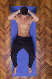 Young fit slim muscular abs man exercise elevated view. Laying mat Stock Images