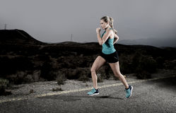 Young fit sport woman running outdoors on asphalt road in mountain fitness workout Royalty Free Stock Photo