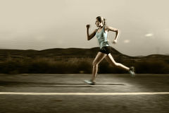 Young fit sport woman running outdoors on asphalt road in mountain landscape and dramatic light set for advertising. Young attractive and fit sport woman running Stock Photography