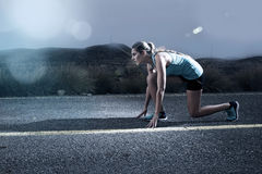 Young fit sport woman running outdoors on asphalt road in mountain landscape and dramatic light set for advertising Stock Photos